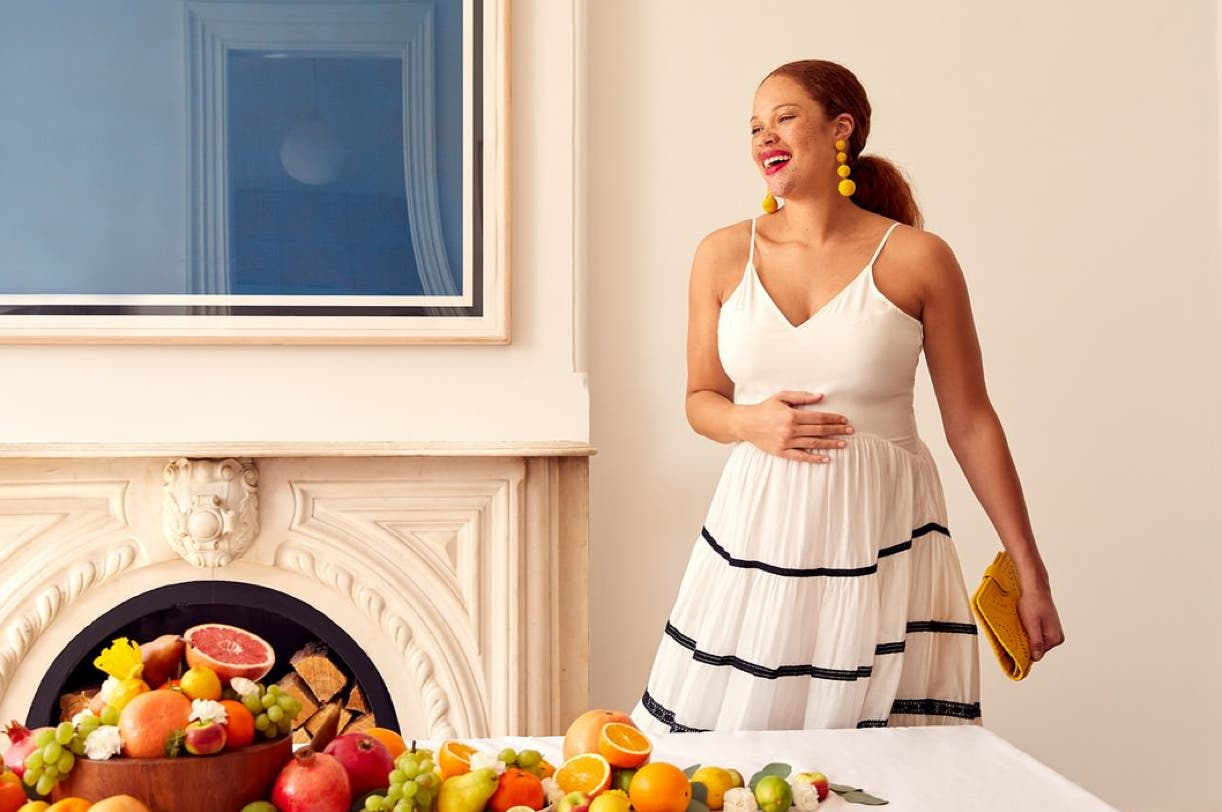 Pregnant woman next to table of fruit.